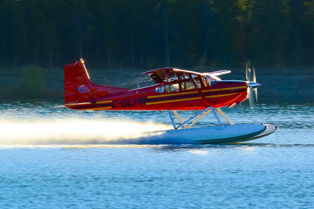 A Cessna 180 takes off into the morning sunrise
