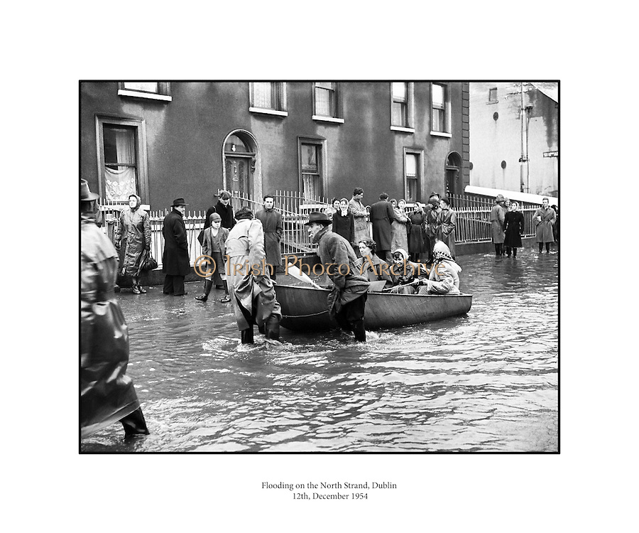 """Flooding at the North Strand, Dublin.8-12/12/1954..From The Irish Times - December 12 2005..SEVERE storms during this week in 1954 brought some of the worst flooding ever seen on the streets of Dublin. Many areas of the city suffered. The north inner city was particularly badly hit..December 7 and 8, 1954, were described in the Irish Press as """"the worst day following the worst night in memory"""". Not surprising, since this was one of the worst storms to hit Dublin in the 20th century...On the night of December 7, Ireland was battered by gale-force winds, blizzards, heavy rain and sleet, bringing much of the country to a standstill. Dublin's road and rail network were closed, and air traffic at Dublin airport was grounded by 60mph winds...VENICE..The North Strand was under so much water that the Dublin Evening Mail described it as being """"more like Venice than Dublin"""". The Strand Cinema was flooded, and the nearby Cusack's Bar was under six feet of water...One local resident - 70-year-old Mrs Bridget O'Brien, who lived at 5 St Brigid's Cottages off the North Strand Road - was trapped in her home by the rising waters and died...The most serious incident in the area occurred at East Wall Road where the GNR metal railway bridge collapsed and fell into the Tolka. Army engineers dynamited the mouth of the river in a bid to clear it of debris from the fallen railway bridge...Hundreds of evacuees were given temporary accommodation in a shelter run by the Saint John's Ambulance at North Strand. Others rendered homeless by the floods were given food and shelter at the Sisters of Charity convent in North William Street...Author Benedict Kiely was a first-hand witness to the devastation caused by the floods at Drumcondra and he described the water rushing past Lemon's sweet factory on the Tolka as an """"Andean Flood""""...Cottage-dwellers living beside the river erected a statue of the Madonna in front of their flooded houses and christened her Our Lady of the Floods...One Fairview wom"""