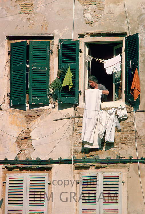 A woman hanging out washing in Corfu.