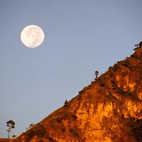 Americas, Central American, Guatemala, Lake Atitlan. A full moon rises over the volcanic peaks of Lago Atitlan in Guatemala.
