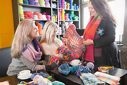 Knitting teacher with two women in knitting lesson shows scarf, Bavaria, Germany