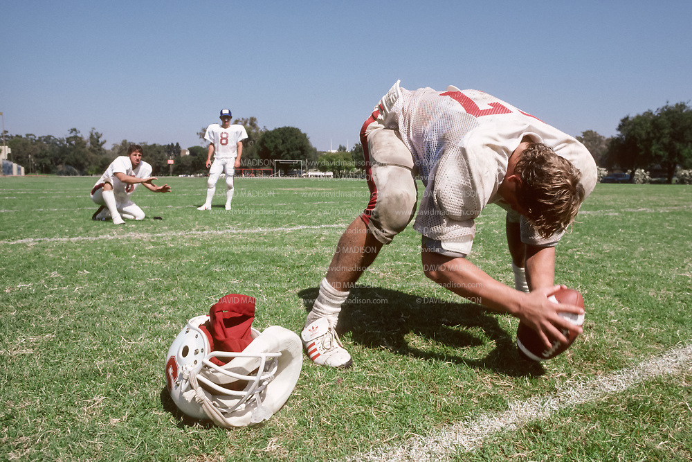 COLLEGE FOOTBALL:  Mike Teeuws #57 of Stanford practices long snaps during September 1981 at Stanford University un Palo Alto, California.  Steve Cottrell #6 and Mark Harmon #8 await the snap.   Photograph by David Madison ( www.davidmadison.com ).