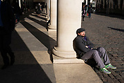 Man relaxing in the sunshine against one of the columns in Covent Garden London, UK.
