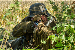 A reenactor portraying a german sniper, wearing a tan & water pattern camouflage smock, M42 stahlhelm and using a K98 sniper rifle with scope