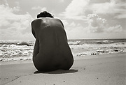 Rear view of nude woman sitting hunched over on beach meditating with surf