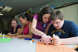 Teachers helping students with learning disabilities in art class,