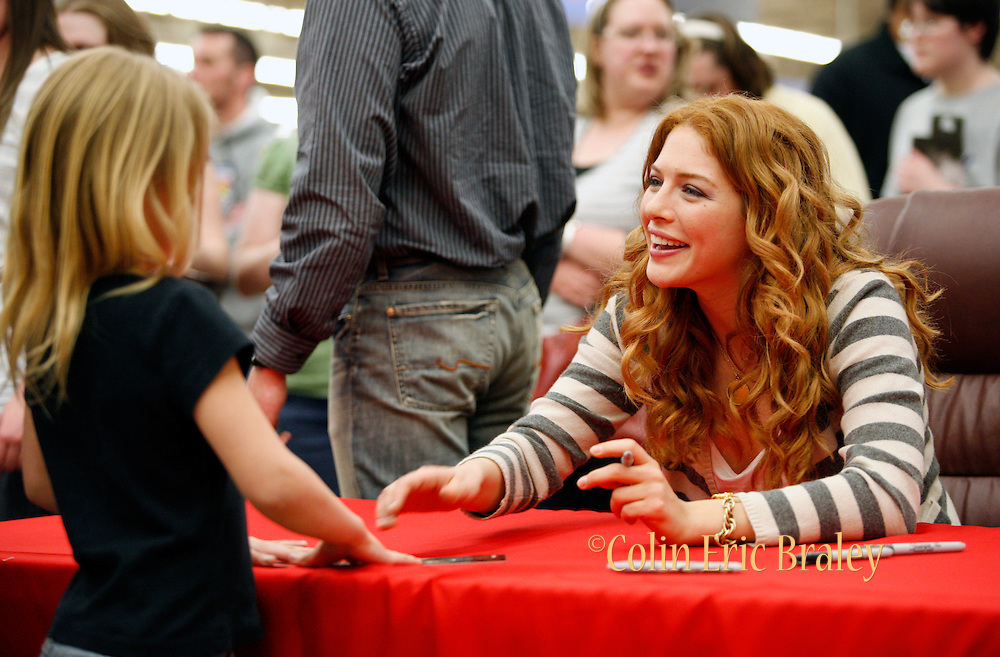 Twilight star Rachelle Lefevre, right, who plays the character Victoria, signs autographs for fans at the Walmart store in Riverton, Utah during the midnight DVD movie release event March 21, 2009. (AP Photo/Colin Braley)