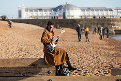 © Licensed to London News Pictures. 02/01/2017. Brighton, UK. A young musician is playing guitar while enjoying the sunshine on the beach as dry and sunny weather is hitting the seaside resort. Photo credit: Hugo Michiels/LNP