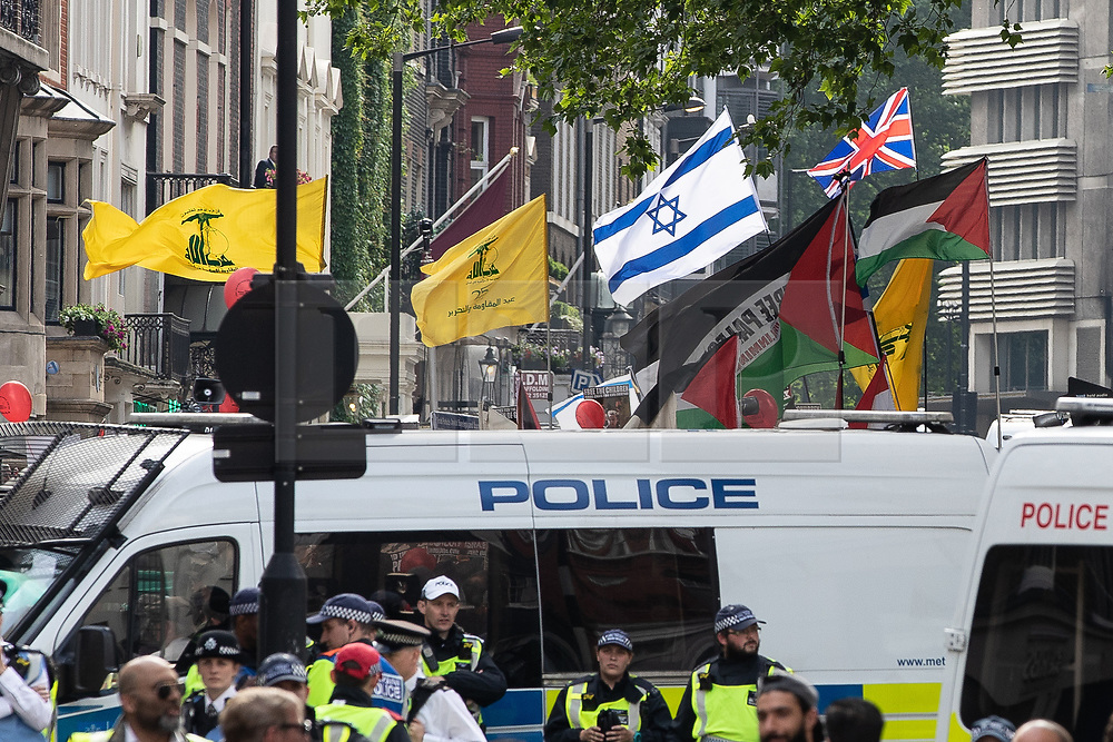 © Licensed to London News Pictures. 10/06/2018. London, UK. Israeli and British flags are flown by counter-demonstrators , behind Hezbollah and Palestinian flags at the annual Al Quds day march in support of the Palestinian cause, in central London. Photo credit: Joel Goodman/LNP