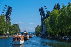United States, Washington, Seattle. Washington, Seattle.  May 2, 2015. Boats pass under the Montlake drawbridge in the canal between Lake Union and Lake Washington on Opening Day of Boating Season.