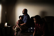 BIRMINGHAM, AL – JUNE 9, 2020: Clarence John Hill, Jr. (center) sits in his living room with his 7 year-old daughter, Jada, and 13 year-old son, CJ. The burial flag honoring his veteran father, Clarence John Hill, Sr., who served honorably in World War II and the Korean War, rests between them. Hill discovered his father had tested positive for coronavirus only after his death, through a funeral home in Alexander City. CREDIT: Bob Miller for The Wall Street Journal<br /> VETVIRUS