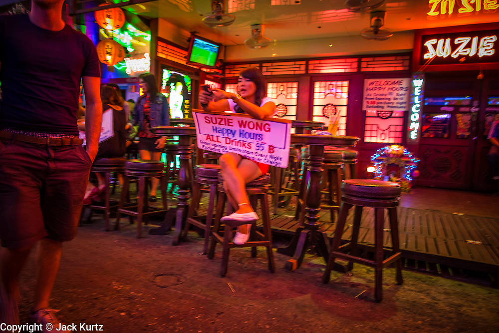 """12 JANUARY 2013 - BANGKOK, THAILAND:  A tout tries to draw tourists into Suzie Wong, a go-go bar on Soi Cowboy in Bangkok. Prostitution in Thailand is illegal, although in practice it is tolerated and partly regulated. Prostitution is practiced openly throughout the country. The number of prostitutes is difficult to determine, estimates vary widely. Since the Vietnam War, Thailand has gained international notoriety among travelers from many countries as a sex tourism destination. One estimate published in 2003 placed the trade at US$ 4.3 billion per year or about three percent of the Thai economy. It has been suggested that at least 10% of tourist dollars may be spent on the sex trade. According to a 2001 report by the World Health Organisation: """"There are between 150,000 and 200,000 sex workers (in Thailand).""""    PHOTO BY JACK KURTZ"""