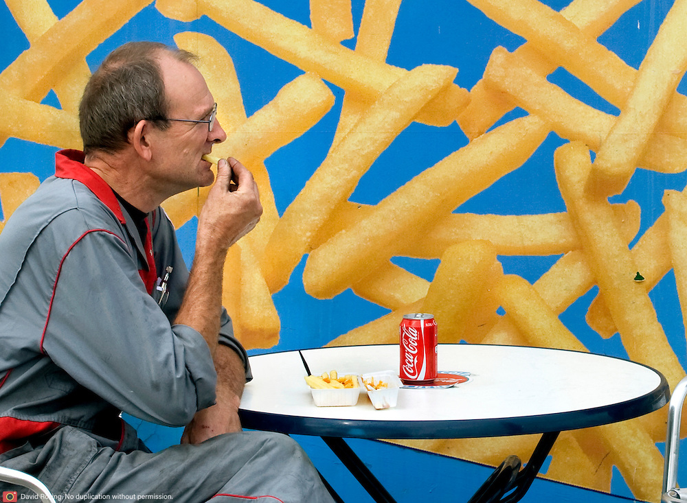 Nederland Rotterdam 5 september 2008 Foto: David Rozing.Man eet friet met frikandel bij frietkot in de europoort..Foto David Rozing