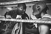 NAIROBI, KENYA - MARCH 18, 2010: A coach preps an athlete between rounds during a boxing tournament featuring the Kibera Olympic Boxing Club, Kenya Prisons and the Kenya Police and Armed Forces (AFABA). Each year, Kibera Olympic boxers aspire individually to make the national team, and the opportunity to compete in the annual Kenya Open boxing tournament. In previous years, boxers from Kibera slum have gone on to win tournaments on both the national and international stage.<br />