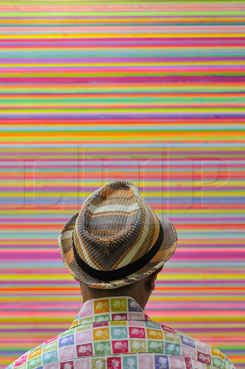 """© Licensed to London News Pictures. 06/10/2017. London, UK.  A visitor views """"Interference Metallic Violet Pink Green"""", 2017,  by Colin McCallum at The Other Art Fair, presented by Saatchi Art, taking place at the Old Truman Brewery in East London from 5 to 8 October 2017.  The fair brings 130 artists, hand selected by a panel of experts, to present their works for sale directly to the public. Photo credit : Stephen Chung/LNP"""