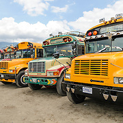 A line of brightly painted old American school buses converted into chicken buses converge in the lot behind the city market.