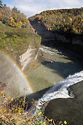 """Middle Genesee Falls rainbow, Portage Canyon, Letchworth State Park, Portageville, New York, USA. In Letchworth State Park, renowned as the """"Grand Canyon of the East,"""" the Genesee River roars northeast through a gorge over three major waterfalls between cliffs as high as 550 feet, surrounded by diverse forests which turn bright fall colors in the last three weeks of October. The large park stretches 17 miles between Portageville and Mount Morris in the state of New York, USA. Drive or hike to many scenic viewpoints along the west side of the gorge. The best walk is along Gorge Trail #1 above Portage Canyon from Lower Genesee Falls (70 ft high), to Inspiration Point, to Middle Genesee Falls (tallest, 107 ft), to Upper Genesee Falls (70 ft high). High above Upper Falls is the railroad trestle of Portageville Bridge, built in 1875, to be replaced 2015-2016. Geologic history: in the Devonian Period (360 to 420 million years ago), sediments from the ancestral Appalachian mountains eroded into an ancient inland sea and became the bedrock (mostly shales with some layers of limestone and sandstone plus marine fossils) now exposed in the gorge. Genesee River Gorge is very young, as it was cut after the last continental glacier diverted the river only 10,000 years ago. The native Seneca people were largely forced out after the American Revolutionary War, as they had been allies of the defeated British. Letchworth's huge campground has 270 generously-spaced electric sites."""