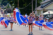 03 JULY 2021 - NORWALK, IOWA: The flag team from Norwalk HIgh School performs during the 4th of July parade in Norwalk, Iowa. Last year's parade was cancelled because of the COVID-19 pandemic. Norwalk is an agricultural community south of Des Moines. In recent years, Norwalk has become a suburb of Des Moines.     PHOTO BY JACK KURTZ