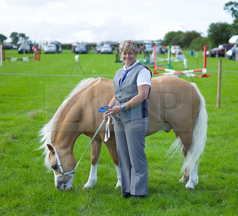 © Licensed to London News Pictures. <br /> 13/08/2014. <br /> <br /> Danby, North Yorkshire, United Kingdom<br /> <br /> A woman stands with her pony prior to judging at the Danby Agricultural Show in North Yorkshire. <br /> <br /> This year is the 154th show which was founded in 1848. It is the oldest agricultural show in the area and offers sheep dog trials, judging of a variety of different animals such as cattle, sheep, ferrets, horses and rabbits along with different classes of horticulture and dairy. <br /> <br /> Photo credit : Ian Forsyth/LNP