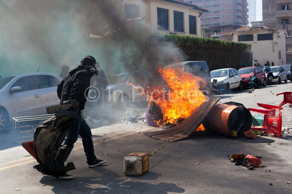 Proesters make flaming barricades and throw projectiles in the street, Police reply with tear gas and stun grenades on the opening day of the FIFA World Cup 2014, several hundred protesters present in Sao Paulo, Brazil. There were some arrests and injuries inlcuding a CNN producer. The protesters were dispearsed relatively quickly due to the Brazilian Police's early show of force.