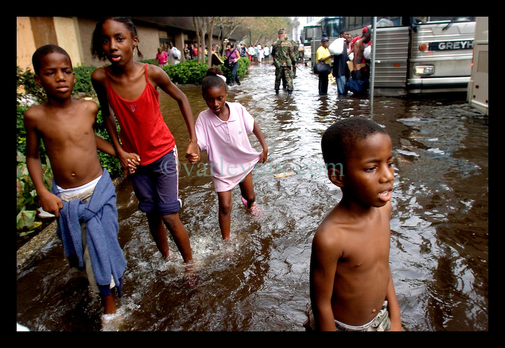 1st Sept, 2005. Hurricane Katrina, New Orleans, Louisiana. Mass evacuation begins. Superdome evacuees start to board the first convoy of busses out of the city. Children wait in the water.