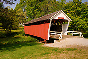 """14 SEPTEMBER 2020 - WINTERSET, IOWA: The Cutler-Donahoe Bridge, built in 1870 near the town of Bevington, IA. The bridge as moved to a park in Winterset in 1970, for the bridge's centennial. The covered bridges of Madison County are an enduring tourist attraction more than 25 years after the book and movie """"The Bridges of Madison County"""" made them famous. There are six covered bridges in Madison County, all built in the 1800s. They are remnants of about 100 covered bridges built in Iowa from the 1850s through the late 1800s. Most of the briges were washed away in floods, condemned, or destroyed in fires. The Madison County bridges have been restored and rebuilt through the years.    PHOTO BY JACK KURTZ"""