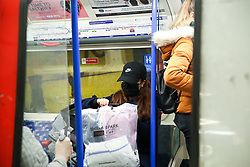 © Licensed to London News Pictures. 13/03/2020. London, UK. A woman wearing a face mask travels on Piccadilly line train amid an increased number of Coronavirus (COVID-19) cases in the UK. A tube train driver has tested positive of the virus. 798 cases have been tested positive and ten patients have died from the virus in the UK. Photo credit: Dinendra Haria/LNP