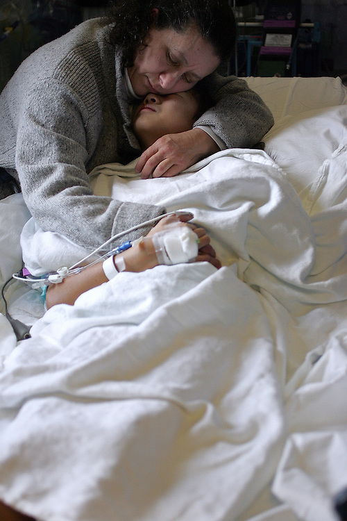 """2/13/2009 Baltimore, MD-  Lani Dickinson, 14, is comforted by her mother Julie Bell in a recovery room at Johns Hopkins Hospital after she underwent surgery for the """"revision of her transhumeral amputation.""""  Lani was born in China with a congenital defect and adopted by an American family.  Despite her disability, she trains hard as a ballerina and would like to someday be a professional dancer.  Photo by Lisa Hornak"""