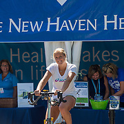 August 22, 2016, New Haven, Connecticut: <br /> Shelby Rogers rides a spin bike at the Yale New Haven Health booth during Day 4 of the 2016 Connecticut Open at the Yale University Tennis Center on Monday August  22, 2016 in New Haven, Connecticut. <br /> (Photo by Billie Weiss/Connecticut Open)