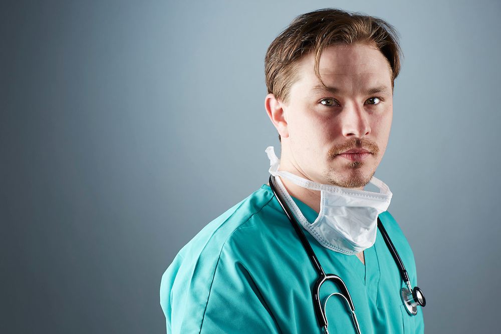 A portrait series representing the intense emotions that Doctors face.  A white male Doctor wearing a white surgical mask, stethoscope, and green medical scrub suit shown.