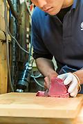 Fishmonger cuts tuna fish for sale at the Tsukiji fish market, largest in the world, Tokyo, Japan