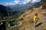 As his mother washes clothes in a communal spring below, a young boy of about 9 years of age stands on a track in the Himalayan foothills near the town of Gorkha. Here, the British army traditionally recruits young men for the Gurkha regiment (as they have done since 1857). The lad is wearing a yellow hooded sweatshirt and like many in this region - even is sub-zero temperatures - flip-flops. Nepal is one of the world's poorest countries. The prospects for this child may mean they will in future, if the army has no place for him, he may try to seek work in cities like Kathmandu rather than face a lifetime's struggle in local agriculture, as can be seen in the valley below. Their supplies and contact with the outside world comes up from these tracks of boulders and stone along which either men or yaks carry up food for basic survival and luxury goods.