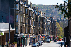 View along a quiet Morningside road with closed shops and cafes during coronavirus lockdown in Edinburgh, Scotland, UK
