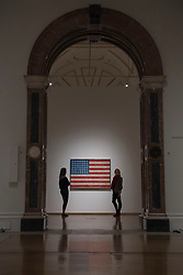 "© Licensed to London News Pictures. 19/09/2017. London, UK. Staff members view ""Flag"", 1958, by Jasper Johns.  Preview of a landmark exhibition by Jasper Johns RA called ""Something Resembling Truth"" at the Royal Academy of Arts in Piccadilly.  Sculptures, drawing, prints plus new works are on display 25 September to 10 December 2017.   Photo credit : Stephen Chung/LNP"