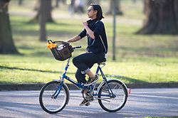 © Licensed to London News Pictures. 27/02/2019. Greenwich, A cyclist pulling her top because she is hot.People out and about in Greenwich Park,Greenwich this afternoon enjoying the February mini winter heatwave as the unseasonably warm weather continues. Photo credit: Grant Falvey/LNP