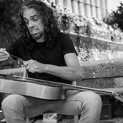 A street guitarist forced to constat his strings need a change