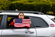 A child holds an American flag out the window of a moving car during a ReOpen PA rally in Harrisburg, Pennsylvania on April 20, 2020.  Protesters gathered at the Pennsylvania Capitol to demand that Governor Tom Wolf reopen the state's economy.