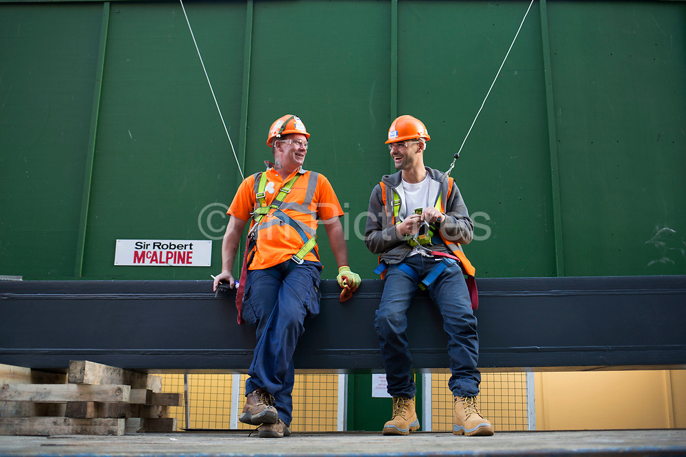 Workmen attached to safety harnesses about to lift a steel girder from the back of a lorry. London, UK. These construction workers laugh together before lifting the 6 ton load onto site.
