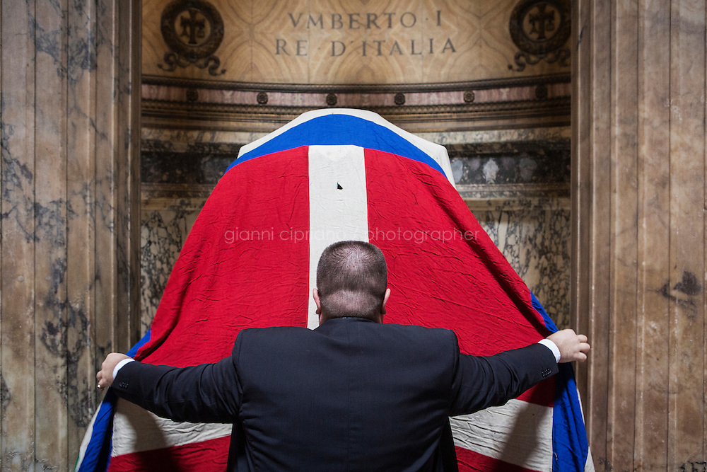 ROME, ITALY - 29 JULY 2014: Alberto di Maria (29), an event organizer and Honor Guard to the royal tombs of the Pantheon,  covers the tomb of Umberto I (King of Italy from 1878 until his death on July 29th 1900) with the flag of the Kingdom of Italy before  a mass to commemorate the anniversary of his death, in Rome, Italy, on July 29th 2014.<br /> <br /> The National Institute for the Honor Guards to the royal tombs of the Pantheon is a monarchic-oriented whose goal is to watch over the royal tombs at the Pantheon. Italy's first king, Vittorio Emanuele II and his son Umberto I, as well as Umberto's wife Queen Margherita are entombed in the Pantheon.