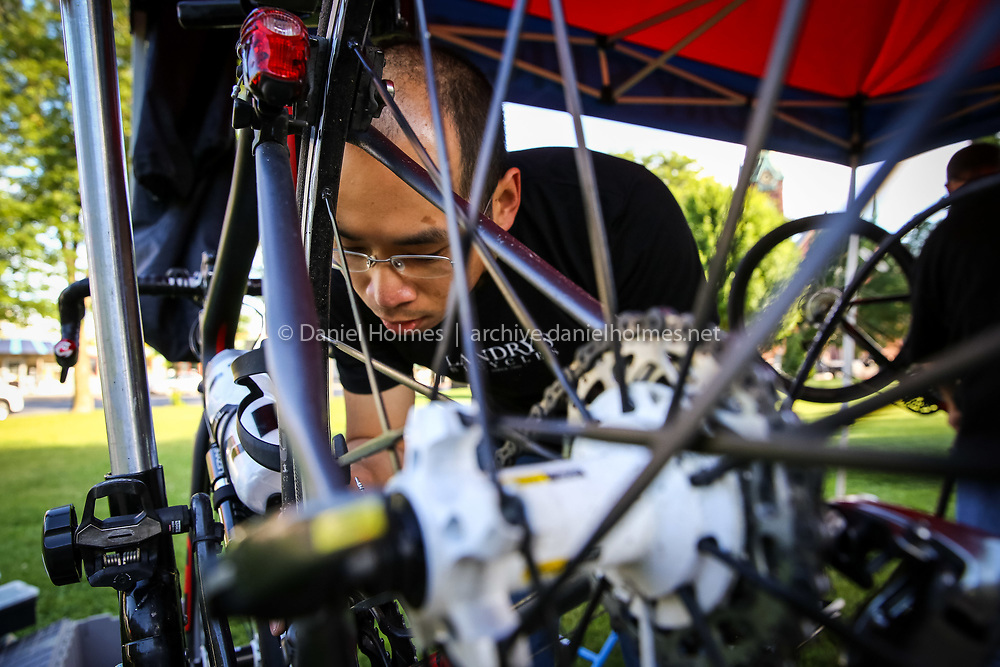 """(6/15/14, NATICK, MA) Douglas Kwan of Landry's Bicycles tunes up a bike during the Natick Rotary Club's 11th Annual """"Tour de Natick"""" bike ride on the Natick Common on Sunday. Daily News and Wicked Local Photo/Dan Holmes"""