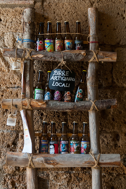 """A display of craft beer in the streets of the village of Civita di Bagnoregio.<br /> Civita di Bagnoregio is a town in the Province of Viterbo in central Italy, a suburb of the comune of Bagnoregio, 1 kilometre (0.6 mi) east from it. It is about 120 kilometres (75 mi) north of Rome. Civita was founded by Etruscans more than 2,500 years ago. Bagnoregio continues as a small but prosperous town, while Civita became known in Italian as La città che muore (""""The Dying Town""""). Civita has only recently been experiencing a tourist revival. The population today varies from about 7 people in winter to more than 100 in summer.The town was placed on the World Monuments Fund's 2006 Watch List of the 100 Most Endangered Sites, because of threats it faces from erosion and unregulated tourism."""