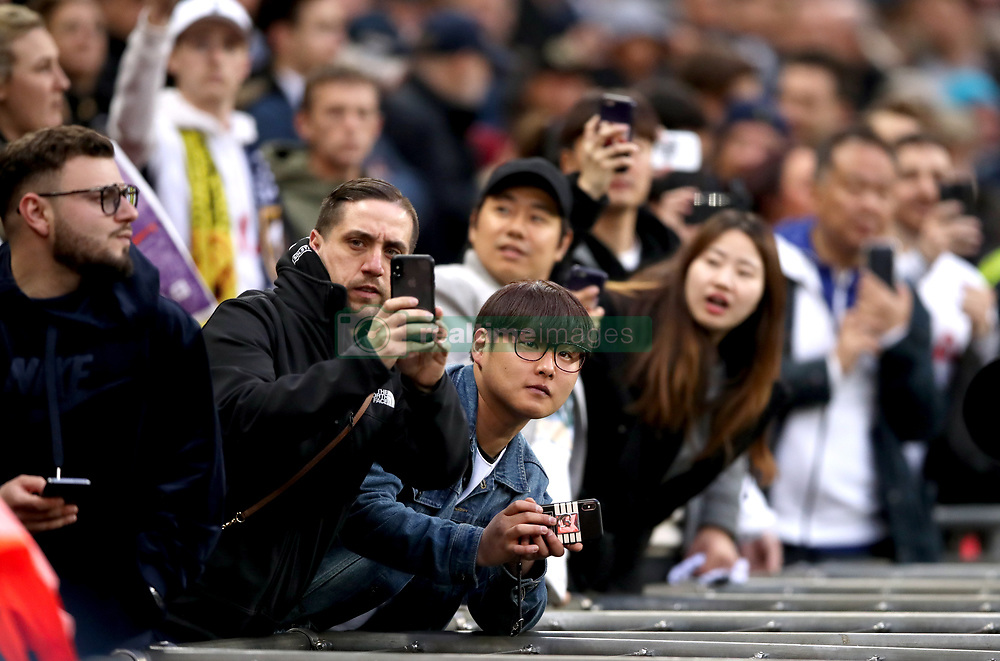 Fans in the stands take pictures on their phones