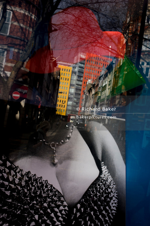 Adult shop costume image and red hat with reflections of central London in the background.