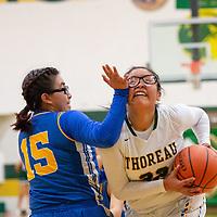 On Thursday in Thoreau, Kayla Garcia (32) of Thoreau is fouled by Kylie Tsikewa (15) of Zuni as she drives to the basket. Thoreau won 65-61.