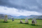 Child runs among stones of Castlerigg Stone Circle near Keswick in the Lake District, Cumbria, England