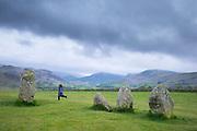 Child runs among stones of Castlerigg Stone Circle near Keswick in the Lake District, Cumbria, England