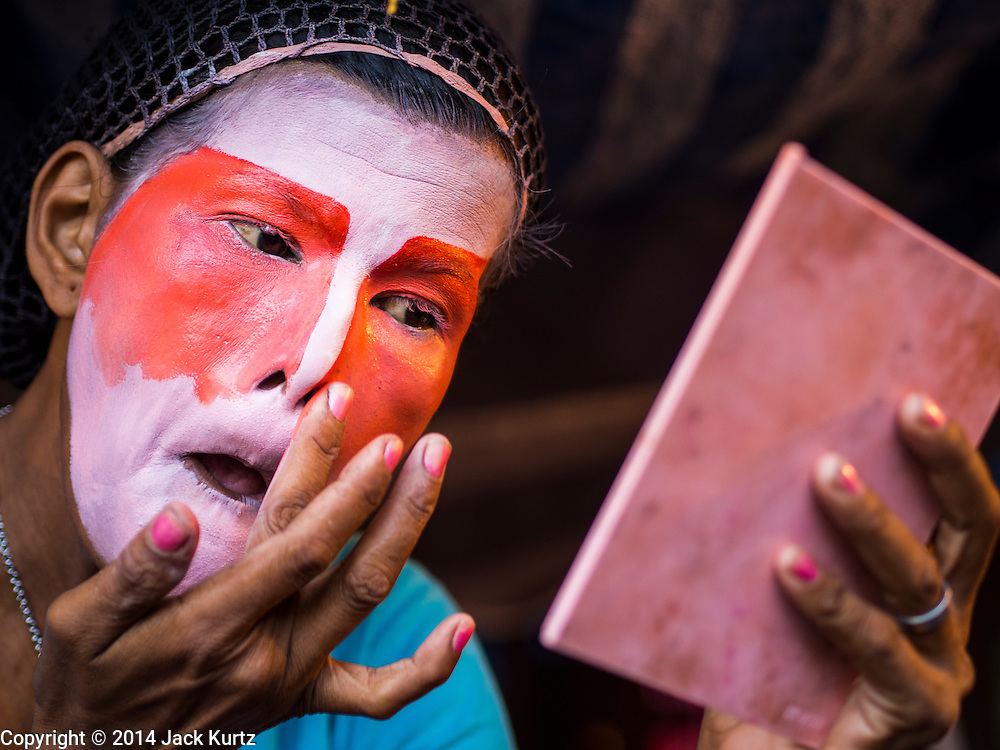 """18 AUGUST 2014 - BANGKOK, THAILAND:   A member of the Lehigh Leng Kaitoung Opera troupe applies her makeup before a performance at Chaomae Thapthim Shrine, a small Chinese shrine in a working class neighborhood of Bangkok. The performance was for Ghost Month. Chinese opera was once very popular in Thailand, where it is called """"Ngiew."""" It is usually performed in the Teochew language. Millions of Chinese emigrated to Thailand (then Siam) in the 18th and 19th centuries and brought their culture with them. Recently the popularity of ngiew has faded as people turn to performances of opera on DVD or movies. There are still as many 30 Chinese opera troupes left in Bangkok and its environs. They are especially busy during Chinese New Year and Chinese holiday when they travel from Chinese temple to Chinese temple performing on stages they put up in streets near the temple, sometimes sleeping on hammocks they sling under their stage. Most of the Chinese operas from Bangkok travel to Malaysia for Ghost Month, leaving just a few to perform in Bangkok.     PHOTO BY JACK KURTZ"""
