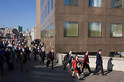 Commuters stream over London Bridge at the outer marker of the City of London, and along a walkway.