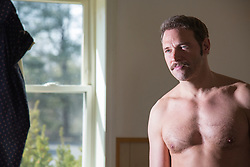 portrait of a handsome man without a shirt in a room with a window