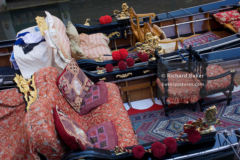 Detail of seats and cushions of a gondola in a narrow canal in Venice, Italy. Current prices (2015) is 80 Euros for a 40-minute journey (earning them approx 130,000 Euros a year) along the waterways of this old city but rarely do gondoliers wear their straw hat.